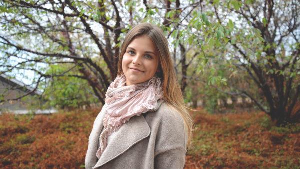 Ung kvinna med trekantig sidensjal med volang i rosa nyanser